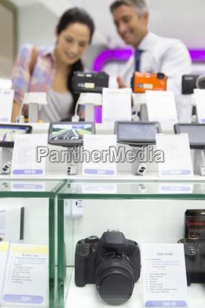 salesman zeigt frau digitalkameras in einem
