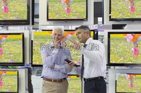 flachbild fernseher hinter verkaeufer und aelterer