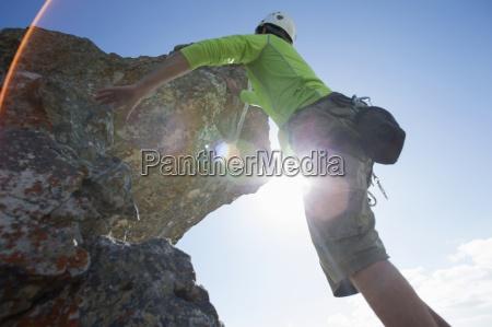 sonne scheint hinter kletterer maennlicher rock