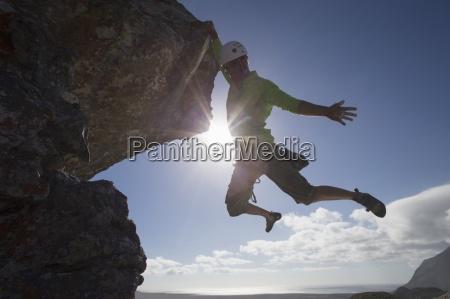 sonne hinter maennlicher rock bergsteiger vom