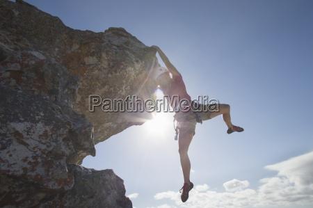sonne hinter weibliche kletterer von rock