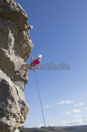 weibliche kletterer abseilen felsen gesicht