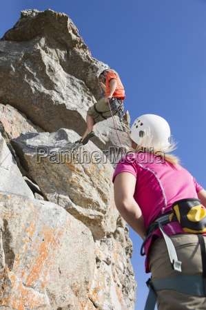 woman watching male rock climber abseiling