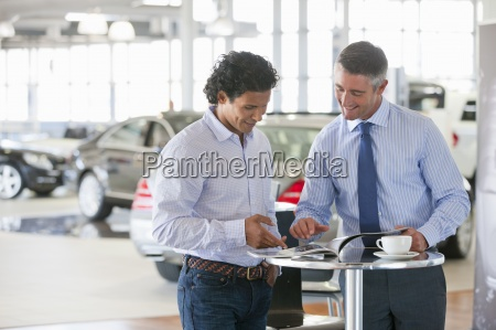 salesman and customer viewing brochure in
