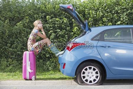 frau mit flach reifen auf auto
