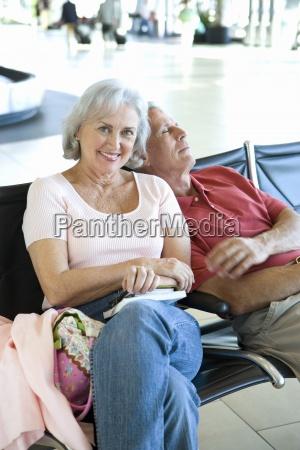 aeltere paare sitzen in flughafen abflughalle