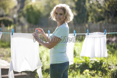 a mature woman pegging out washing