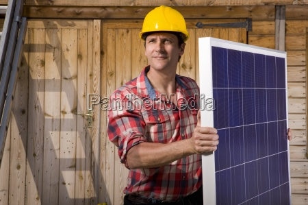 ingenieur haelt solarpanel vor kabine