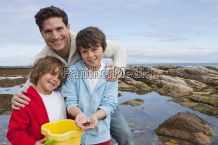 father and sons exploring rockpools together