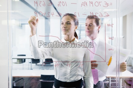 businessman and businesswoman drawing chart on