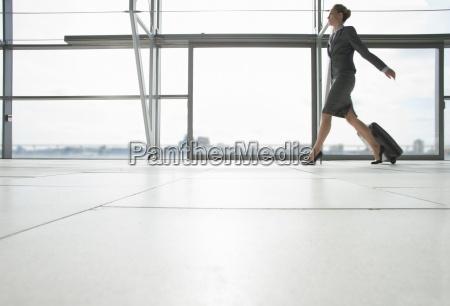 geschaeftsfrau ziehen koffer im flughafen