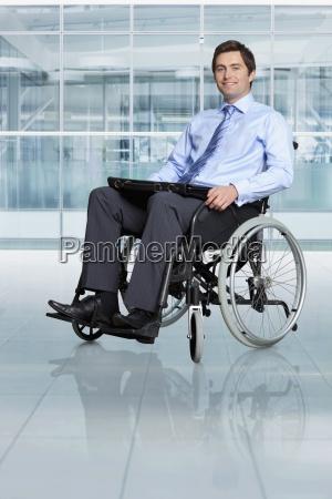 portrait of smiling businessman in wheelchair