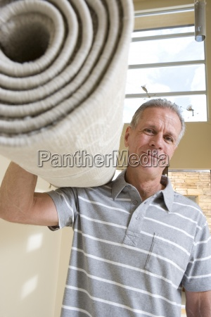 senior man carrying rolled up carpet
