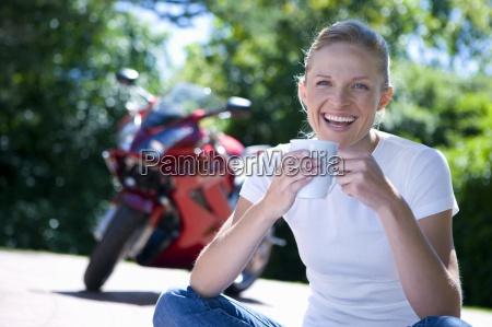 woman sitting on driveway holding mug