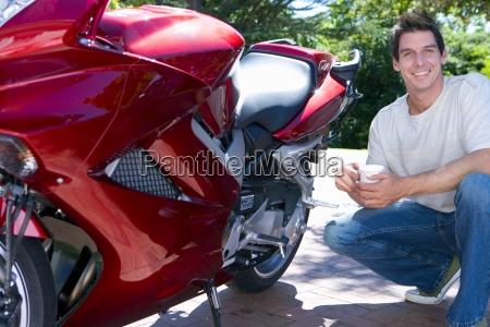 man crouching beside red motorbike on