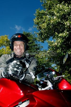 aelterer mann traegt helm und handschuhe