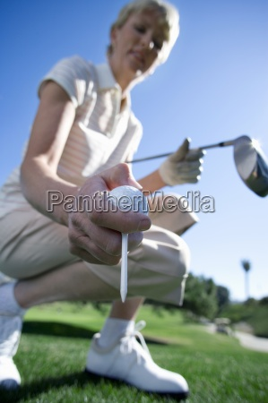 mature woman placing golf tee on