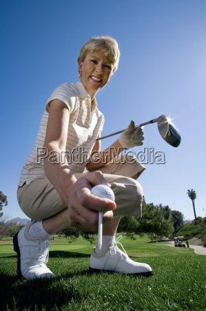 starsza kobieta umieszczenie tee golfowe na