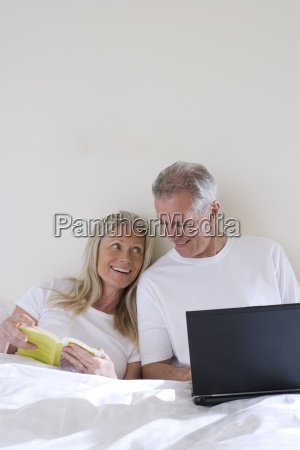 mature couple relaxing in bed woman