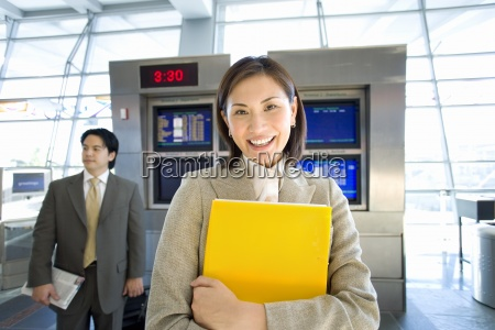 businessman standing near flight information screen