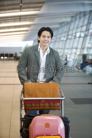 man pushing luggage trolley in airport