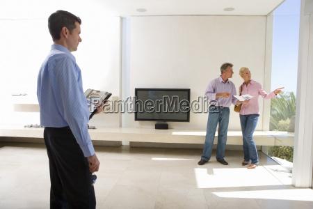 maennlich immobilienmakler suchen aelteres ehepaar stehend