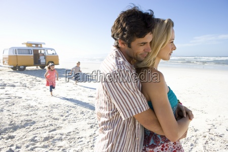 man embracing woman on beach children