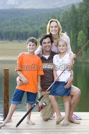 vierkoepfige familie mit angelrute auf jetty
