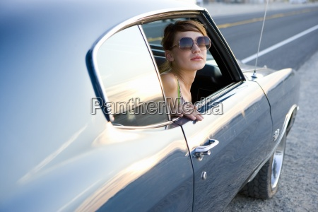 young woman in sunglasses in car