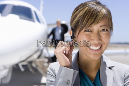 businesswoman with hand on earpiece by