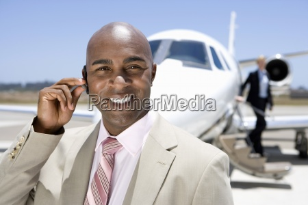 businessman with hand on earpiece by