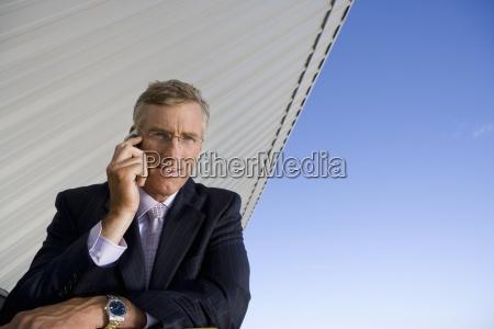 businessman using mobile phone smiling portrait