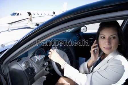 businesswoman using mobile phone in car