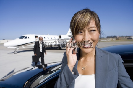 businesswoman using mobile phone by car