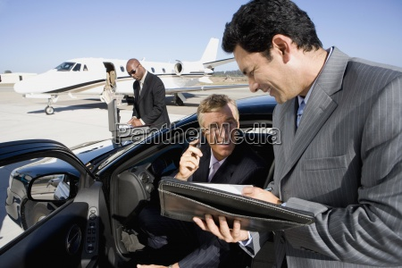 businessman using mobile phone in car