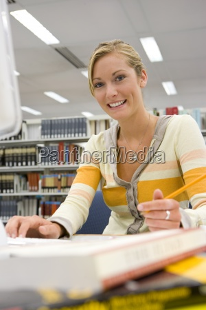 young woman studying at computer in