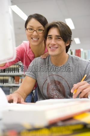 young couple studying at computer in
