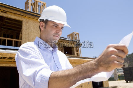 architect with blueprint in front of