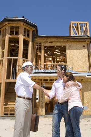 young couple shaking hands with architect