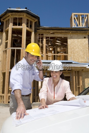 man and woman in hardhats looking