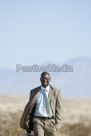 businessman walking in desert smiling portrait