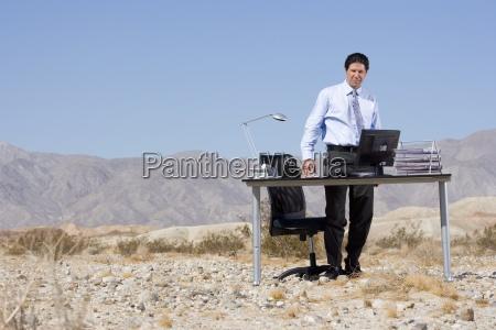 businessman standing by desk in desert