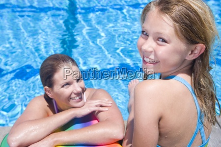 young girl with mother enjoying swimming