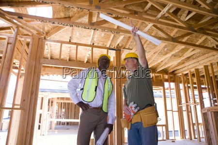 builder in hardhat pointing up to