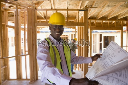businessman in hardhat with blueprints in