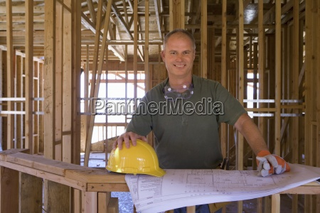 builder with blueprints in partially built