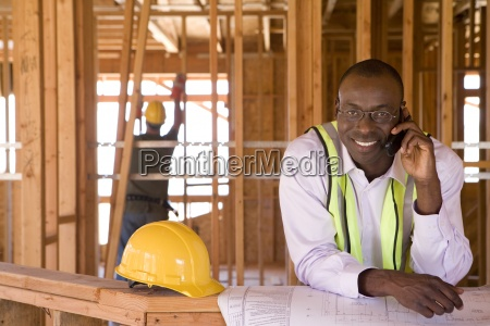 businessman with blueprints using mobile phone