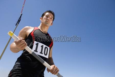junge maennliche athlet mit pole low