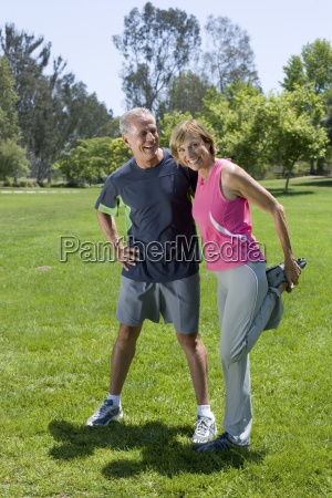 mature couple exercising in park woman