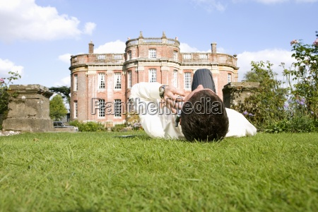 young man lying on grass using